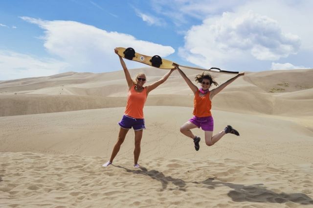 two girls in alamosa sand dune with sand boards